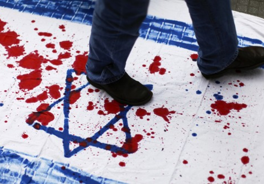 A Venezuelan student walks over a cloth with red paint and the Star of David.