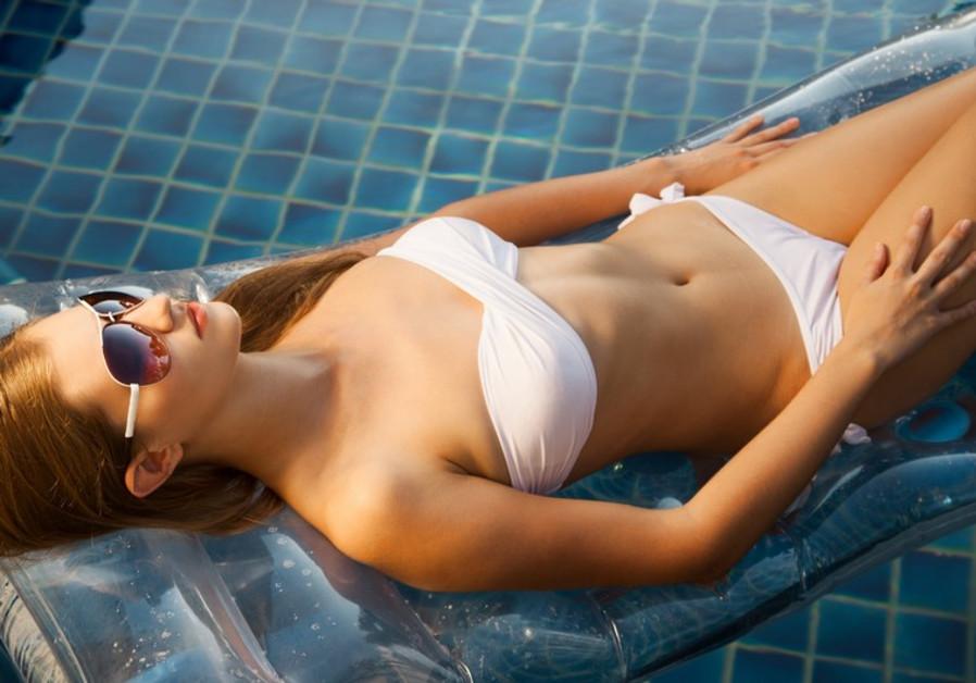 Girl sunbathes poolside [file]