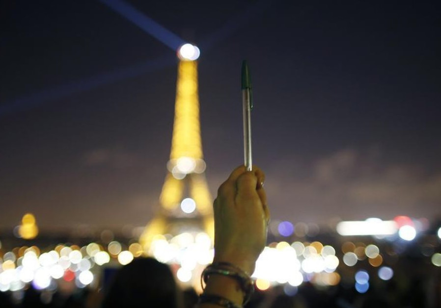A person holds a pen, symbolizing freedom of speech, as lights on the Eiffel Tower start to dim