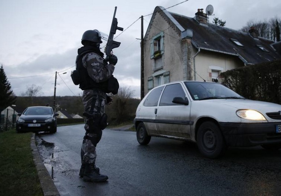 A member of the French GIPN intervention police forces secures a neighborhood northeast of Paris