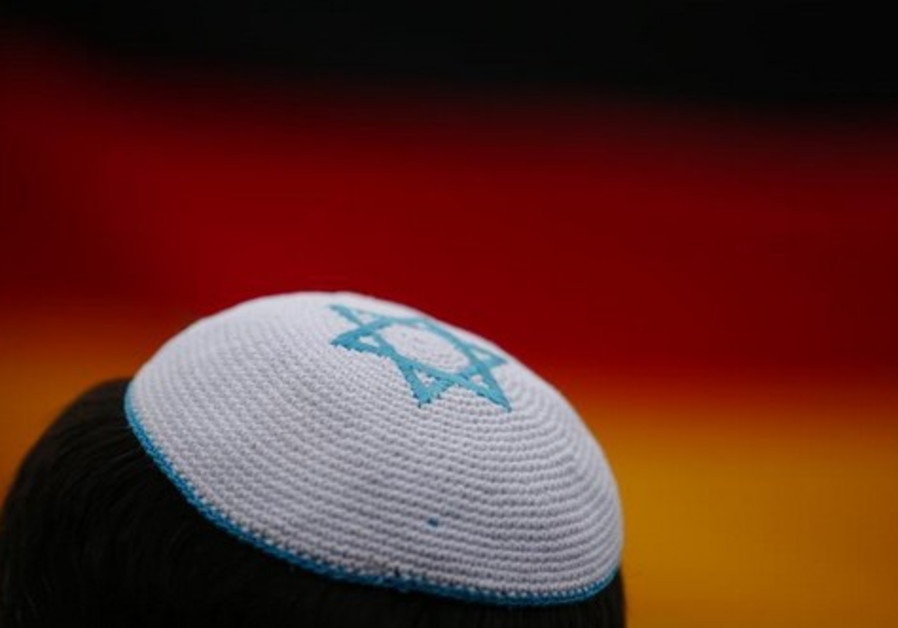 A man wearing a kippah listens to speakers during an anti-Semitism protest at Berlin's Brandenburg G