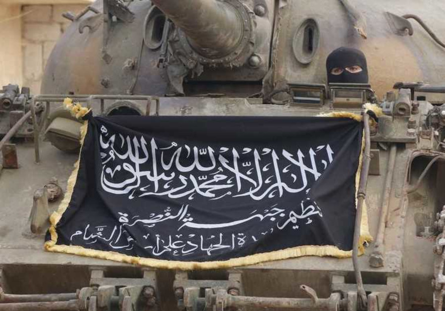 A member of al-Qaida's Nusra Front sits in a tank decorated with the Nusra flag north of Aleppo