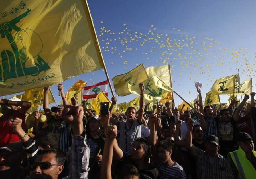People cheer while carrying Hezbollah flags as they celebrate Resistance and Liberation Day