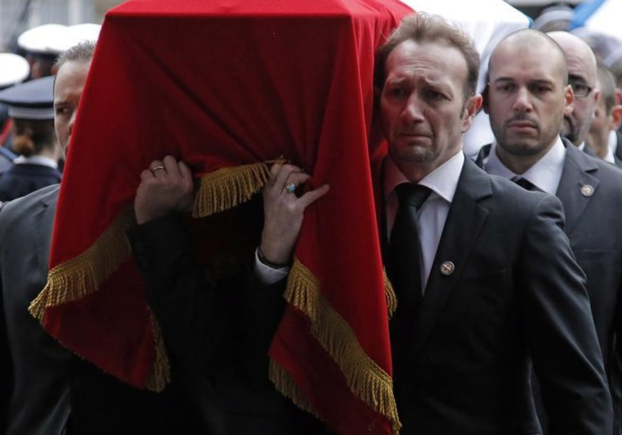 French police officers carry the flag-draped coffin of their late colleague Franck Brinsolaro
