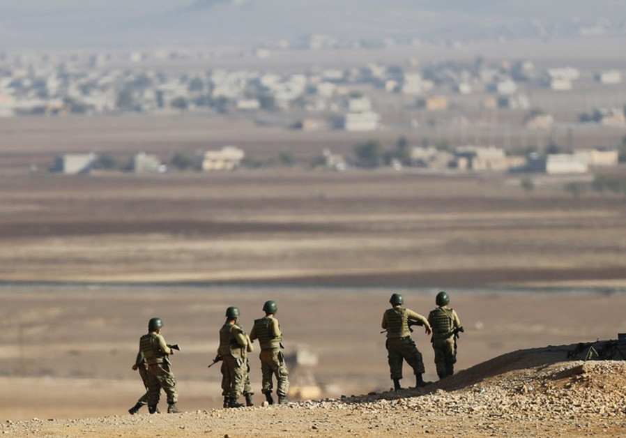 TURKISH SOLDIERS stand guard on the border with Syria.