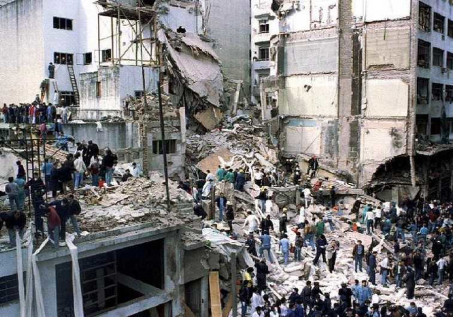 Rescue workers search for survivors and victims in the rubble of the AMIA building