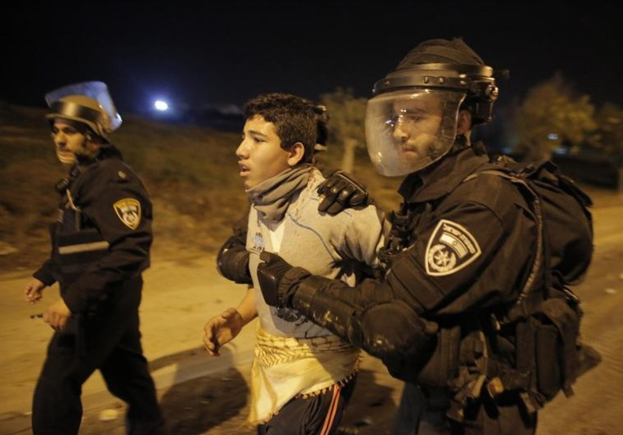 Israeli policemen detain an Arab youth during clashes in the southern town of Rahat