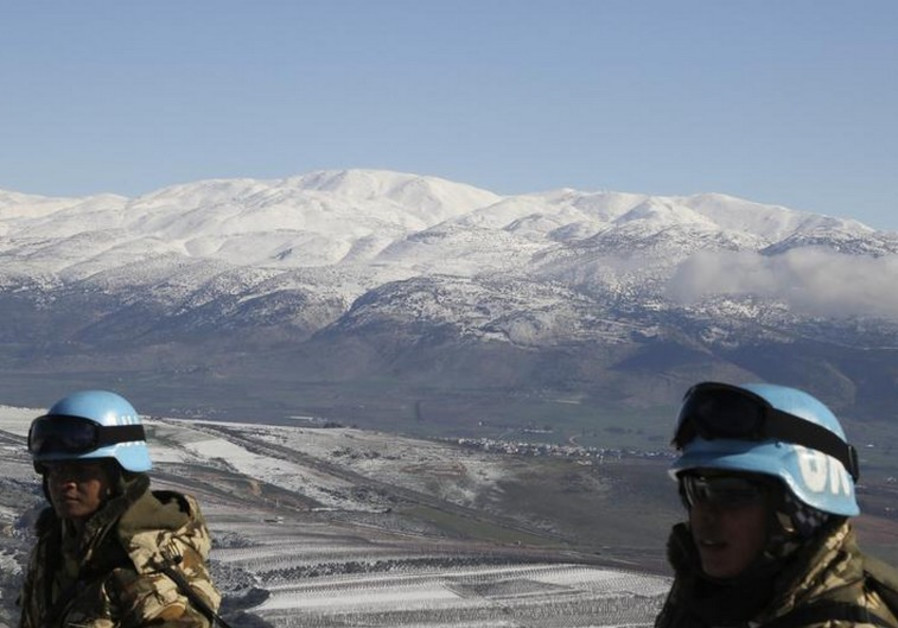 UNIFIL soldiers stand in front of snow-covered mountains in the Kfar Kila village near the border