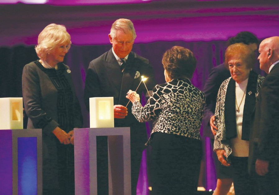 PRINCE CHARLES and a Holocaust survivor light a candle.