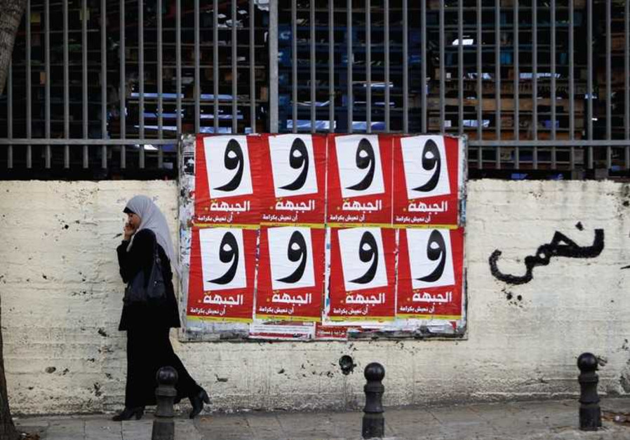 A WOMAN walks past campaign posters for the Arab-led Hadash party in Umm al-Fahm