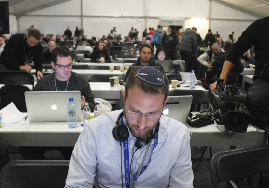 SAM SOKOL works on Tuesday in the press tent set up just outside Auschwitz
