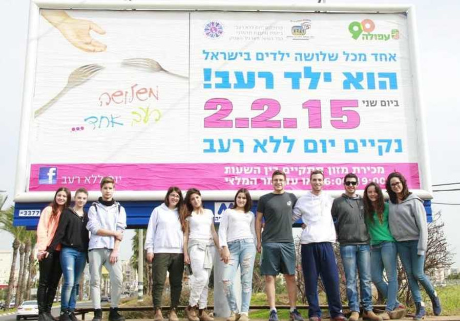WIZO students stand under billboard in Afula for Day without Hunger