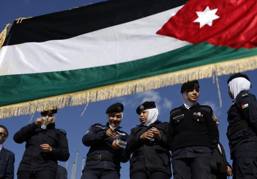 Jordanian police women stand guard near a Jordanian national flag during a pro-monarchy rally