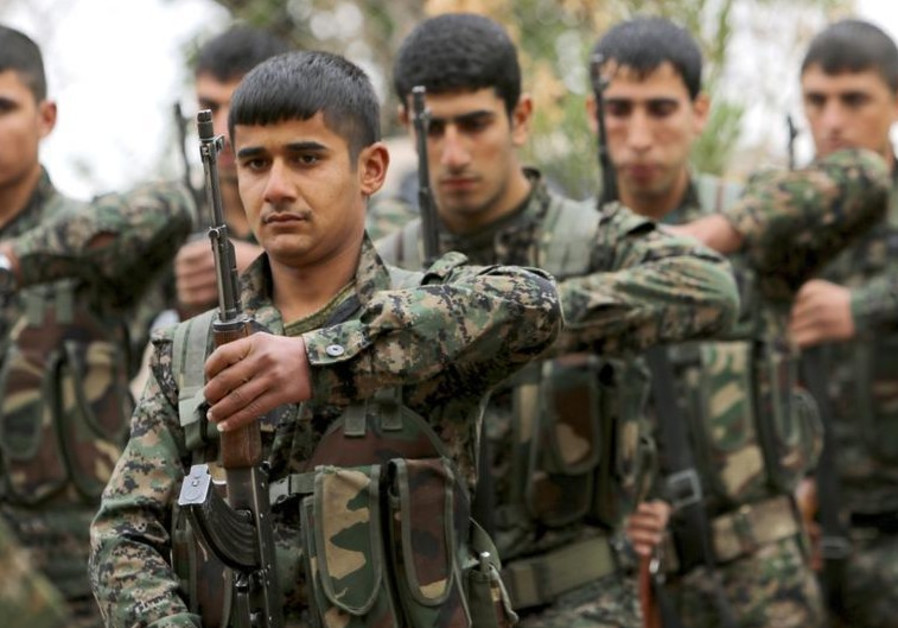 Fighters of the Kurdish People's Protection Units (YPG) carry their weapons at a military training