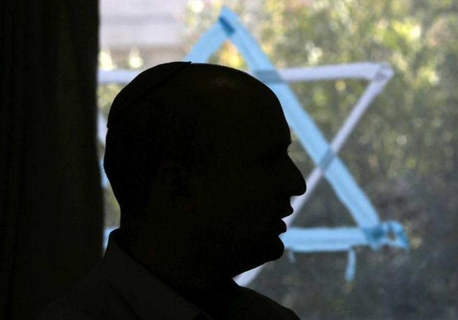 Naftali Bennett, head of the Bayit Yehudi party, is silhouetted during an appearance in Ashkelon