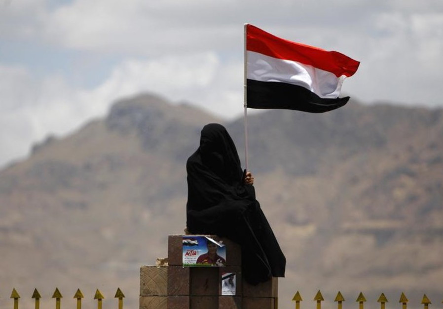 A woman holds the Yemenite national flag