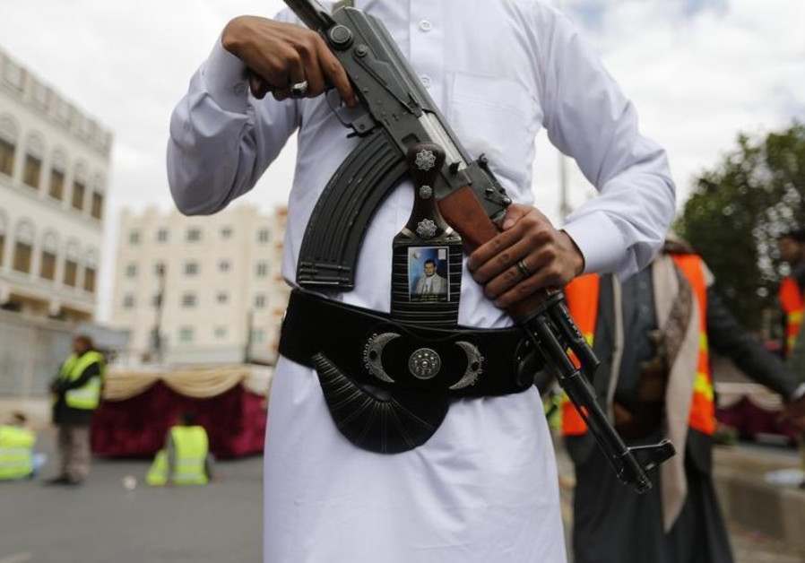 A Shi'ite Houthi militant poses for a photo during a mass funeral for victims of a suicide attack
