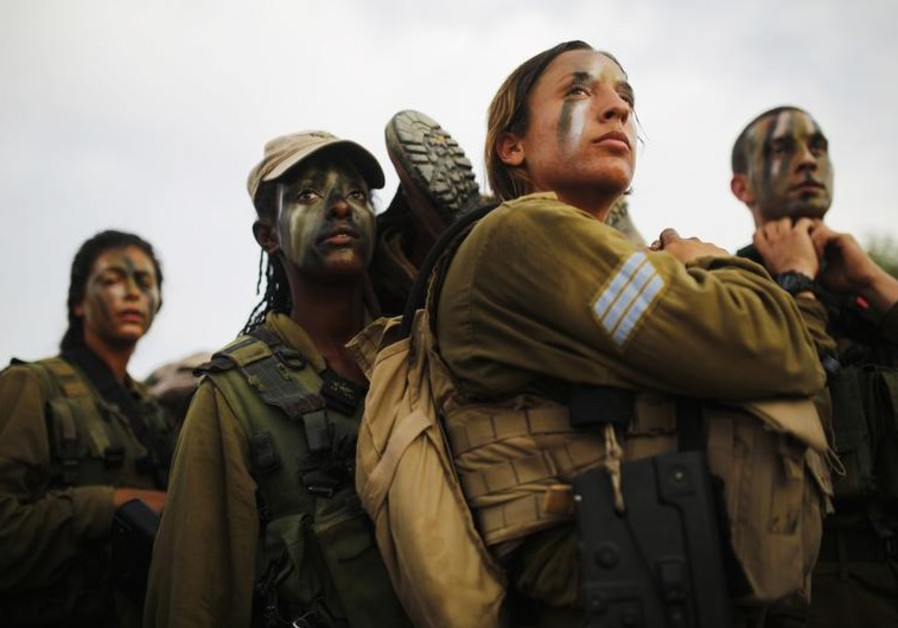 Israeli soldiers of the Caracal battalion carry their comrade on a stretcher during a march
