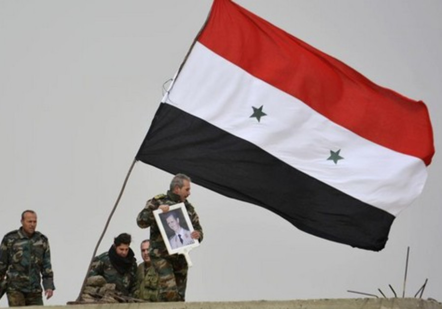 A fighter loyal to Syria's president Bashar Assad holds his picture as fellow fighters rest