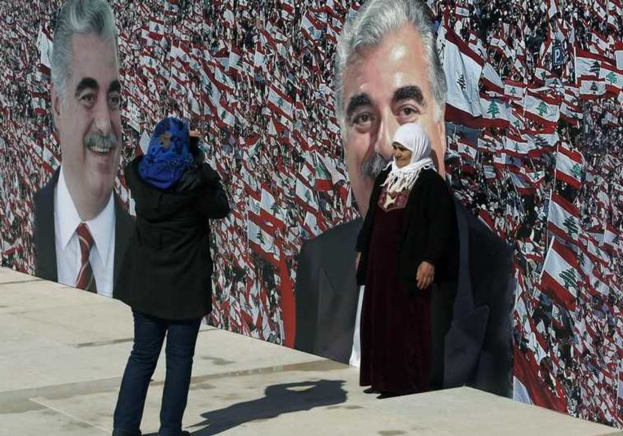 People take a picture near a large banner hanged next to the grave of former Prime Minister Rafik al