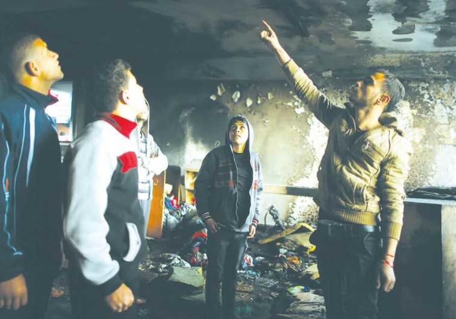 PALESTINIANS INSPECT a burnt classroom at a UN-run school in Gaza