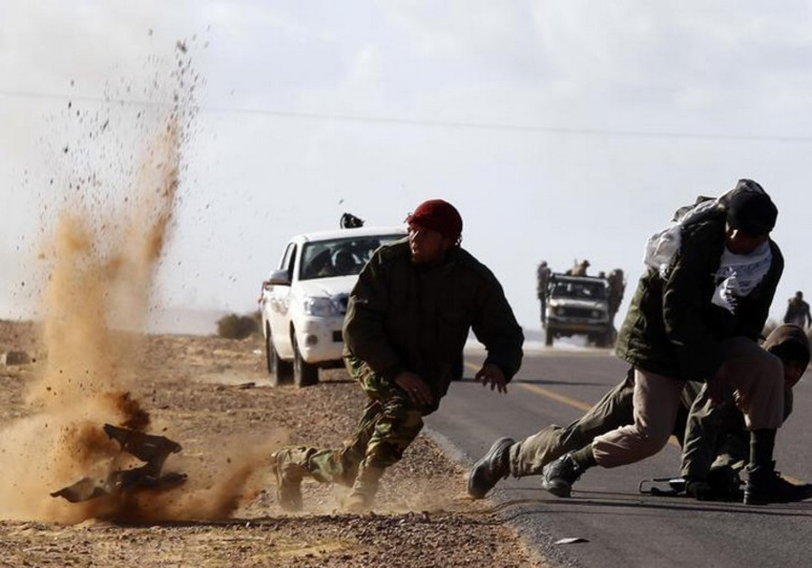 Rebel fighters jump away from shrapnel during heavy shelling by forces loyal to Gaddafi