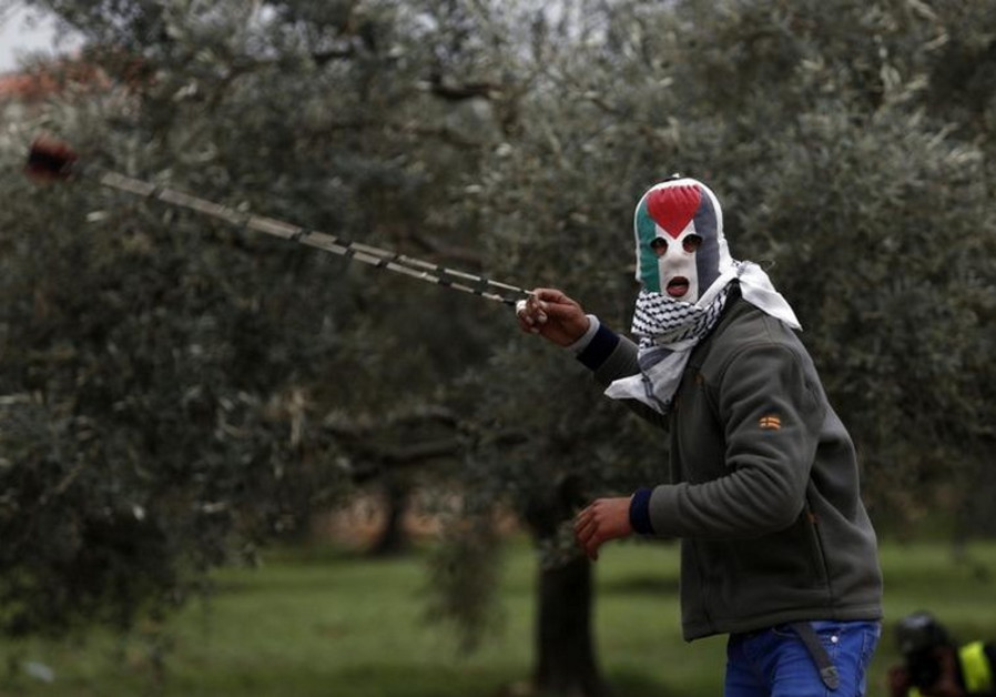 A Palestinian protester wearing a mask featuring the Palestinian flag, uses a slingshot