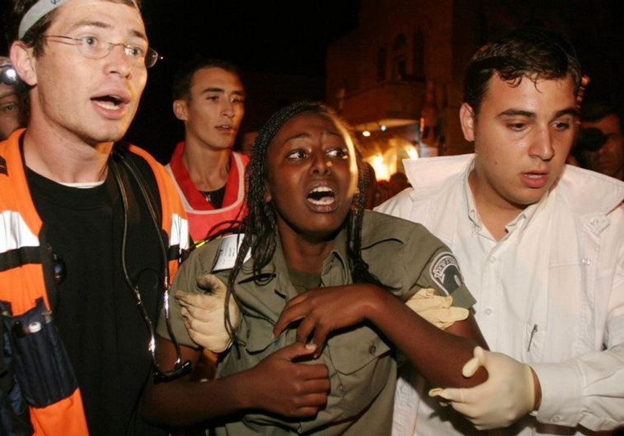 An Israeli Border Policewoman is helped by rescuers after she was injured in a suicide bombing