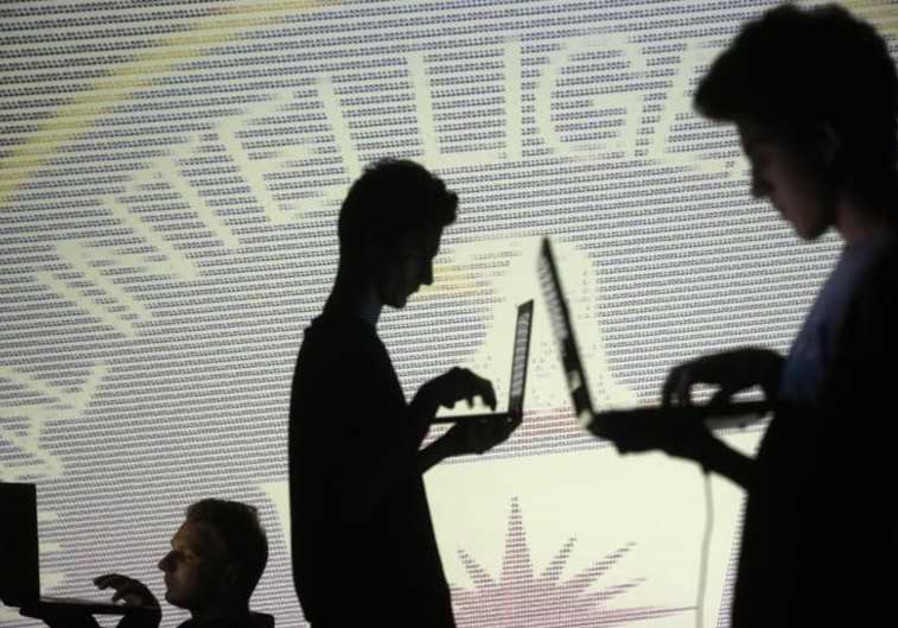 People are silhouetted as they pose with laptops in front of a screen projected with the CIA emblem