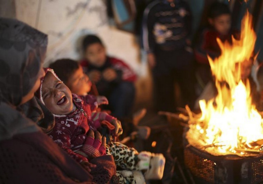 Members of a Palestinian family warm themselves by a fire at the remains of their house