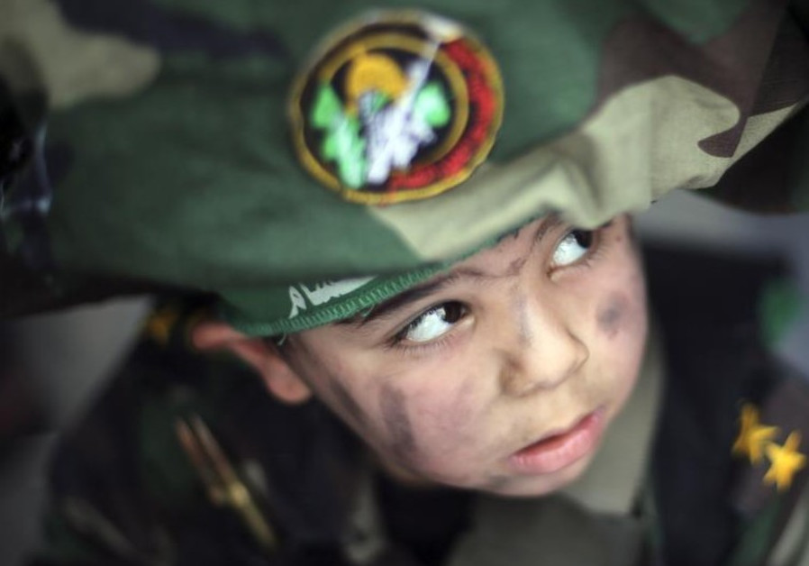 A Palestinian boy wearing the headband of Hamas' armed wing attends Friday prayers in Gaza City
