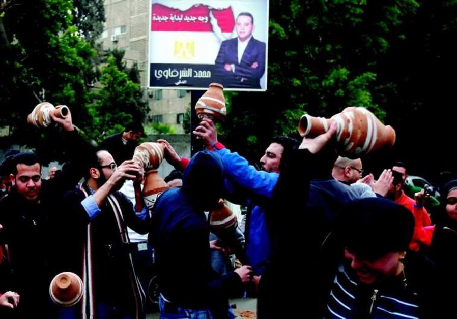 Des Egyptiens en colère cassent de la poterie lors d'une manifestation devant l'ambassade qatarie