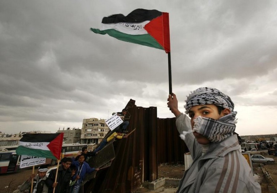 A Palestinian waves a flag near a destroyed section of the border wall between the Gaza Strip and Eg