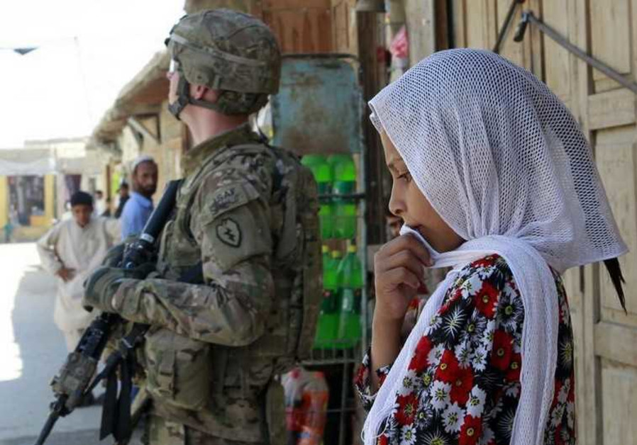 A girl stands next to a US in Jalalabad, Afghanistan