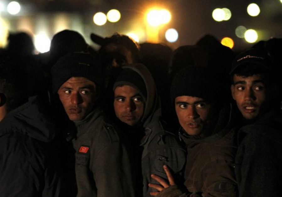 Migrants wait at Italian checkpoint prior to processing
