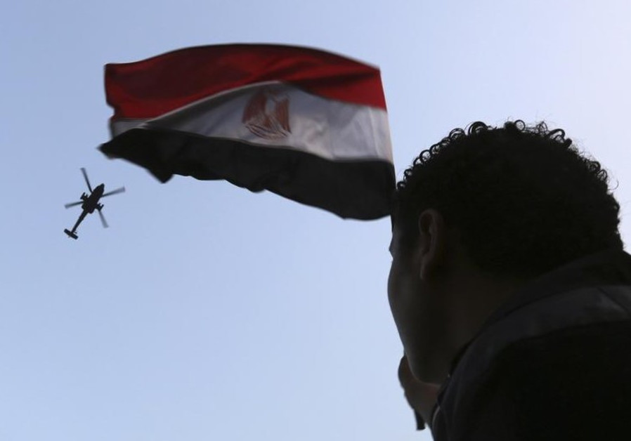 An Egyptian military helicopter, trailing a national flag, circles over Tahrir Square
