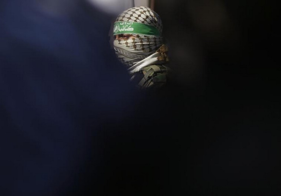 A Palestinian member of Hamas' armed wing takes part in a news conference