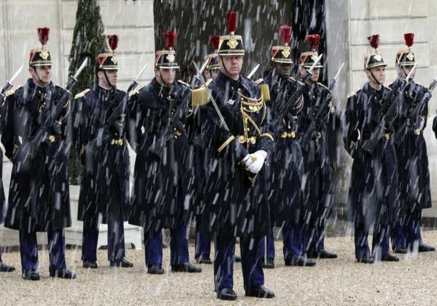 Snowflakes fall as Republican Guards stand in formation in the courtyard of the Elysee Palace