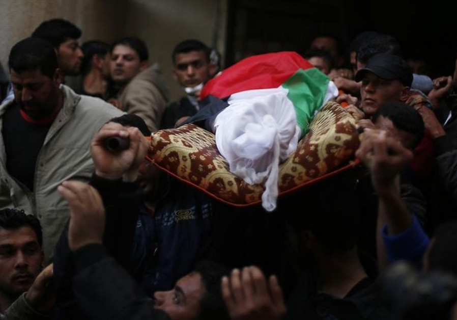 Mourners carry the body of Palestinian fisherman Tawfiq Abu Reyala, 34