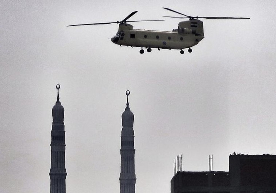 An army helicopter flies over a mosque in Cairo