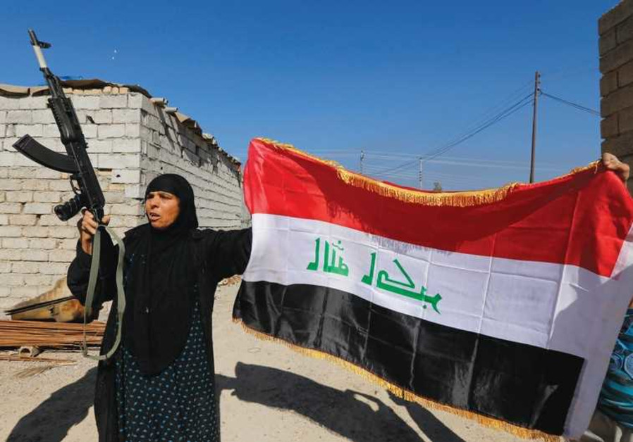 A WOMAN raises a weapon and the Iraqi flag.