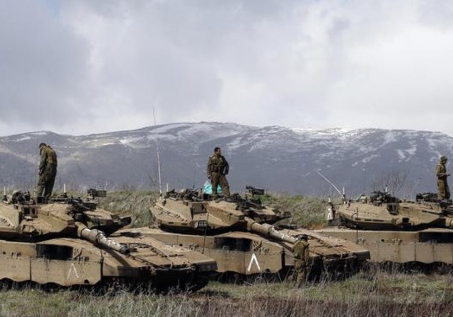 Israeli soldiers stand atop tanks in the Golan Heights near Israel's border with Syria
