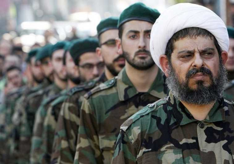 A Shi'ite cleric wearing military uniform with Hezbollah members.