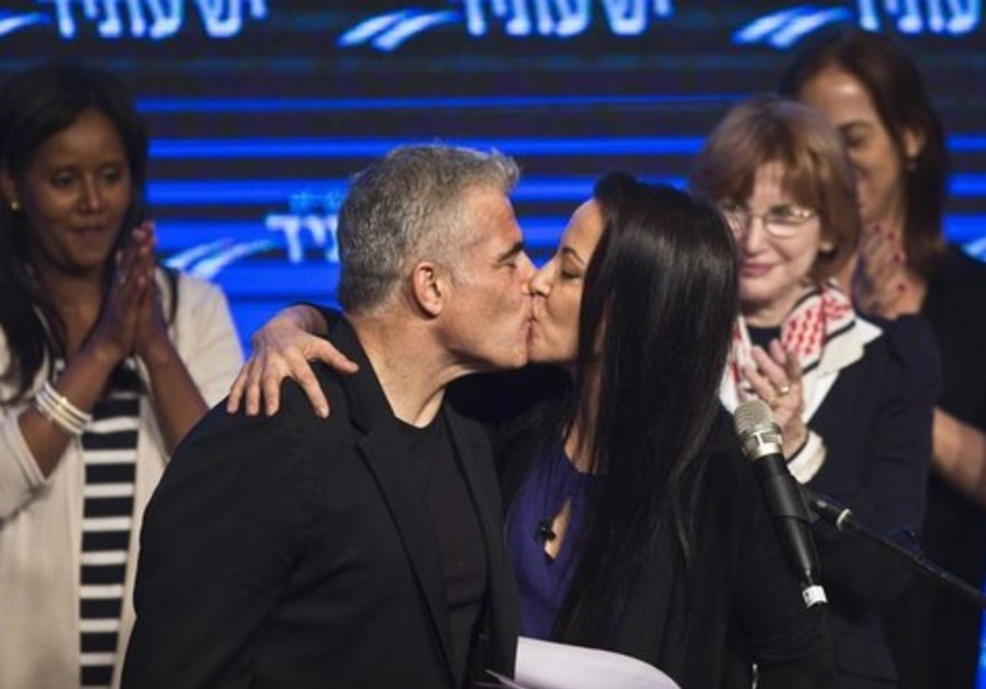 Yesh Atid leader Yair Lapid and his wife Lihi kiss at a women's committee convention in Tel Aviv