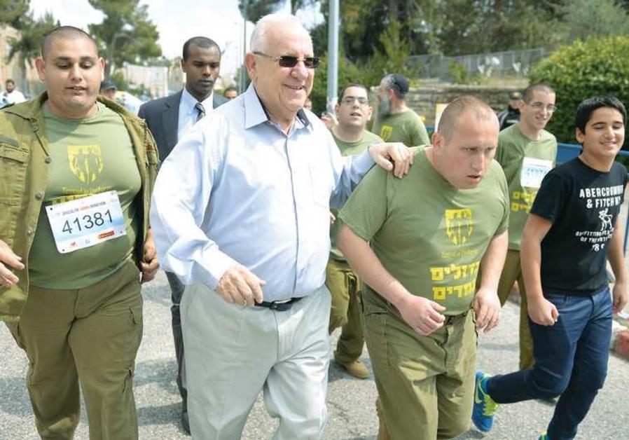 PRESIDENT REUVEN RIVLIN runs a stretch of the Jerusalem Marathon with special-needs kids