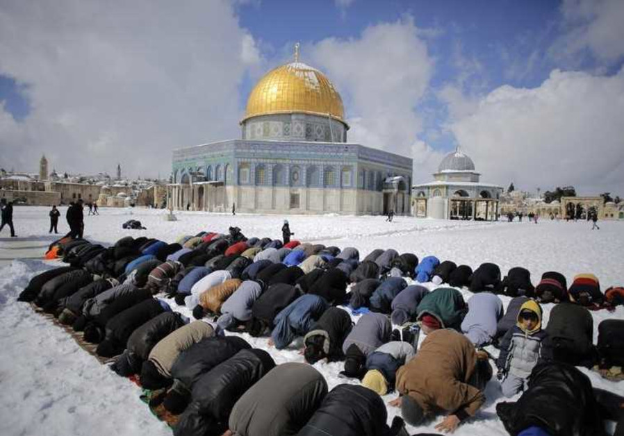 Palestinian men pray in front of the snow-covered Dome of the Rock in Jerusalem's Old City