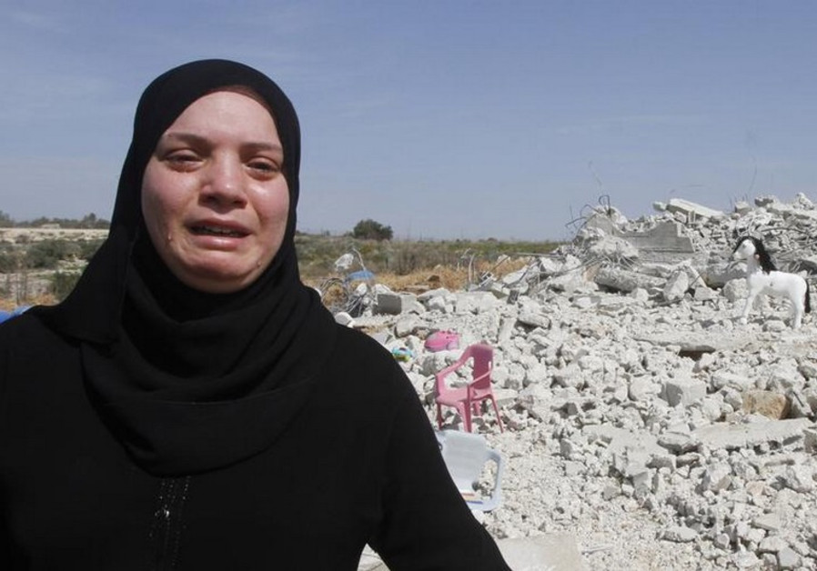 Palestinian woman Taghreed Sholi cries near the rubble of her house that was demolished by the IDF