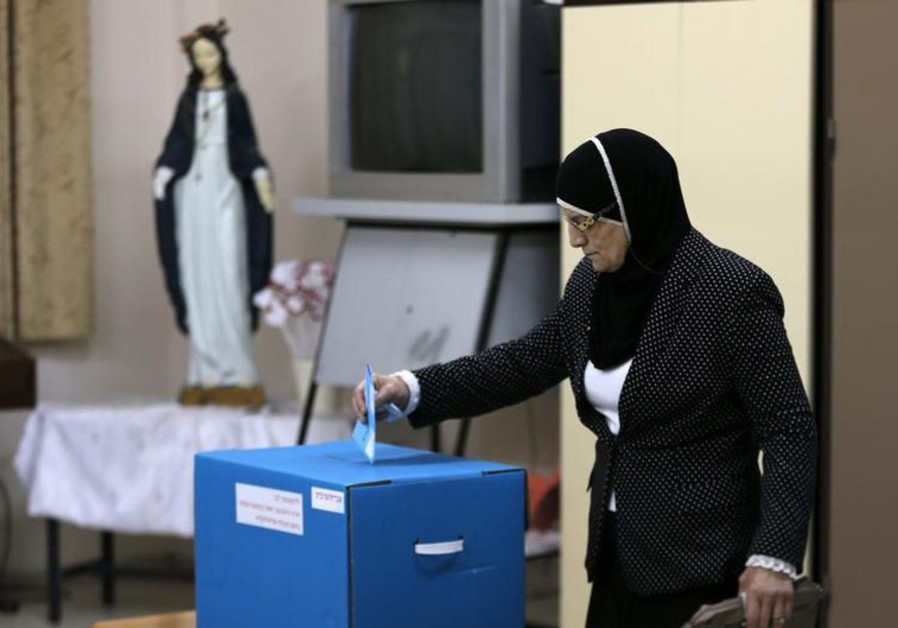 An Israeli Arab casts her ballot at a polling station inside a church in the northern town of Reineh