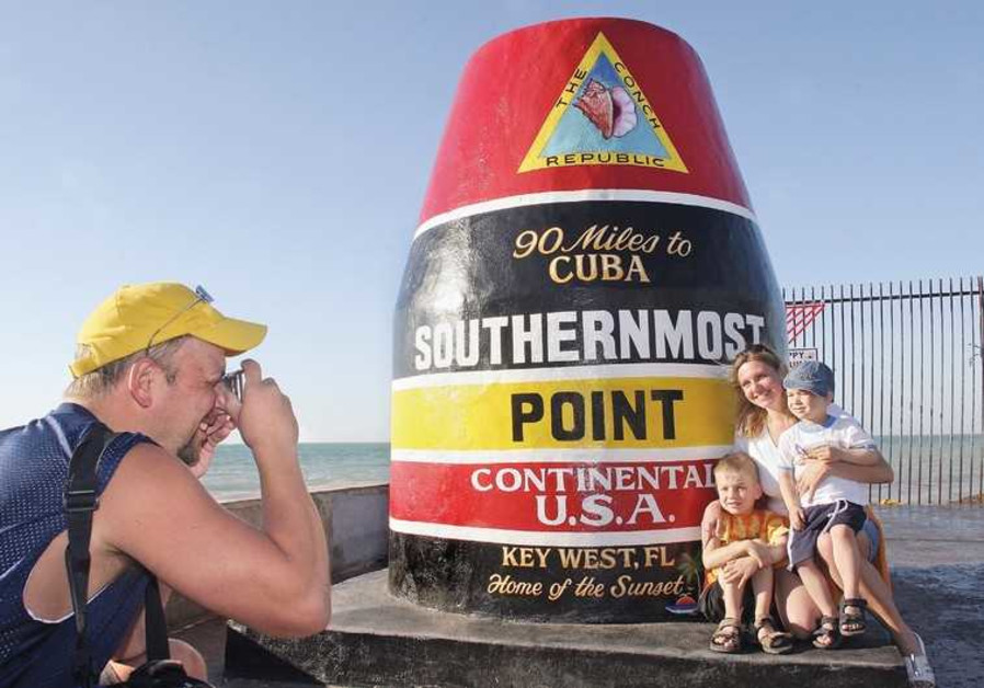 A FAMILY POSES at the southern end of Key West, Florida
