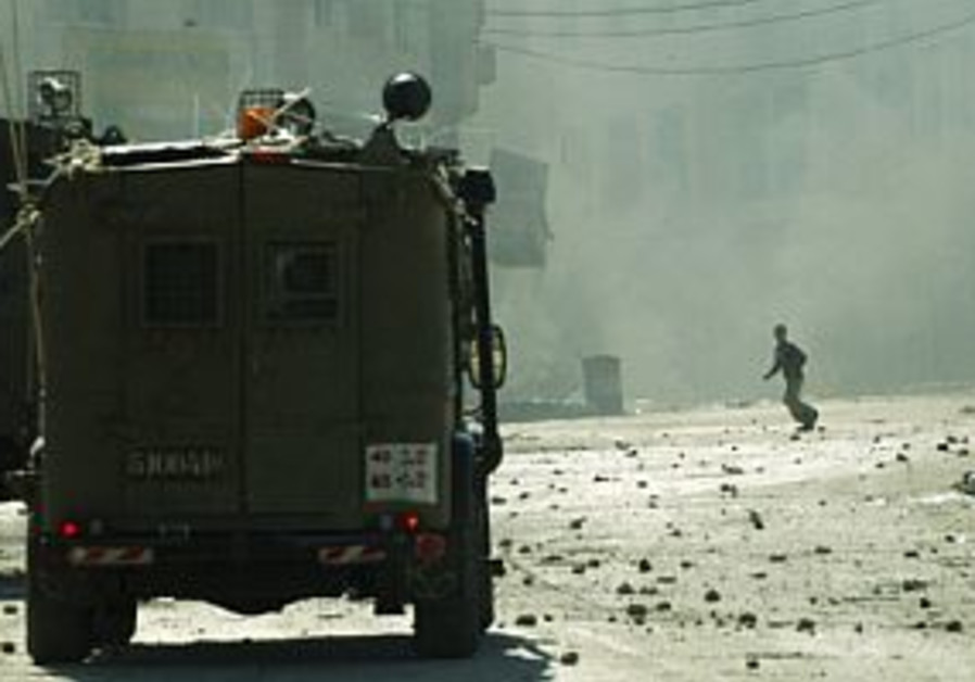 palestinian throws stone at idf jeep 298
